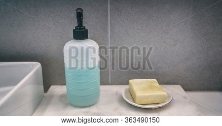 Soap bar versus liquid hand soap bottle comparison of hand washing products on home bathroom vanity counter banner background.