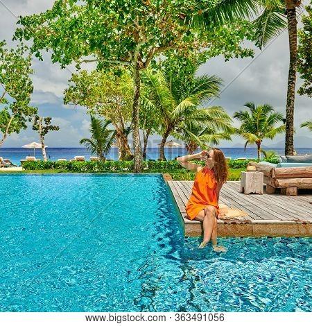 Woman by poolside. Resort swimming pool at Mahe, Seychelles.