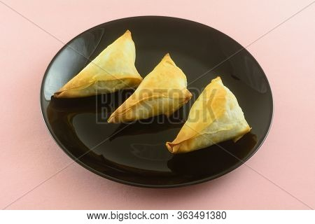 Three Baked Spanakopita Pastry Appetizers On Black Plate With Pink Background