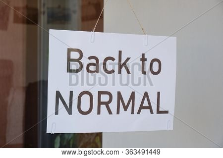 Back To Normal Sign Hanging From A Store Window After Coronavirus (covid-19) Lockdown Measures Are B