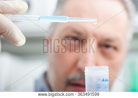 Close-up portrait of a male researcher holding flask with blue liquid in the lab, coronavirus research concept