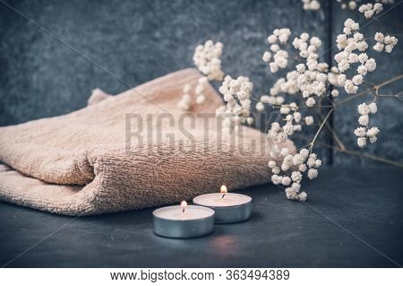 Light Fluffy Beige Towels With Spa Paraphernalia, Candles And Flowers On A Dark Gray Background