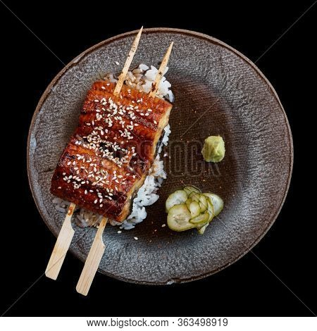 Fried unagi eel with barbecue sauce and rice shot from above isolated on black background