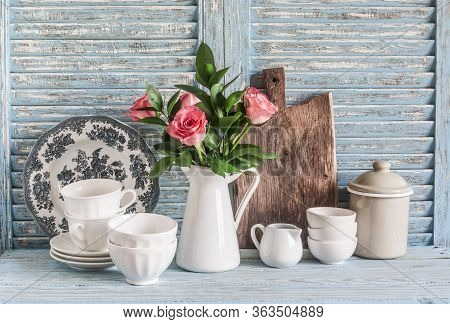Roses In A White Pitcher, Vintage Crockery On Blue Wooden Rustic Background. Kitchen Still Life In V