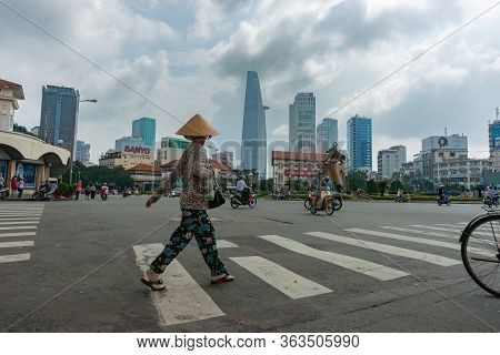 Saigon Vietnam October 12 2013; Woman In Traditional Asian Style Conical Hat Crosses Road In A Busy