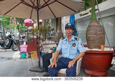 Saigon Vietnam - October 12 2013;   Security Guard Sitting Outside Business Surrounded By Street Clu