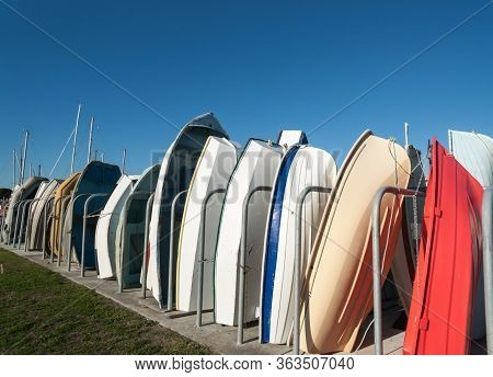 Row Of Dinghy Boats Standing On End In Boat Rack Under Blue Sky.