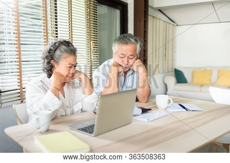 Worried Senior Man And Woman Having Problem About Debts. Stressed Asian Elderly Couple Calculate The