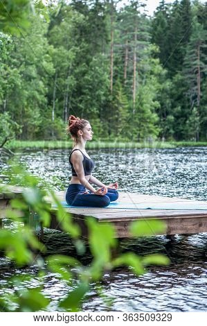 Beautiful Girl In A Yoga Pose On The Lake. Lotus Position ,  Padmasana. The Concept Of Appeasement,