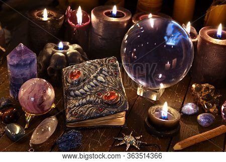 Crystal Ball, Magic Book And Burning Black Candles On Witch Table. Wicca, Esoteric And Occult Backgr