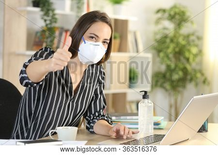 Woman With Thumbs Up Wearing Protective Mask Teleworking With Laptop In Coronavirus Quarantine Sitti