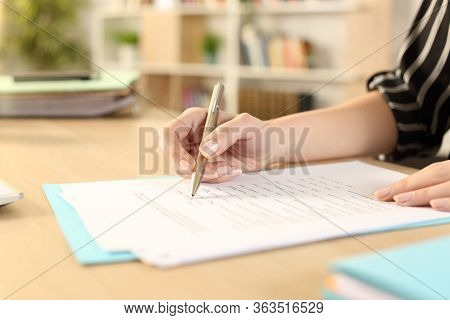 Close Up Of Woman Hands Filling Out Form Working Sitting On A Desk At Home