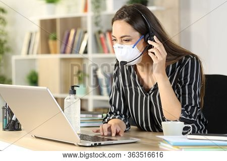 Telemarketer With Laptop Wearing Protective Mask Working At Home Office Due Covid-19