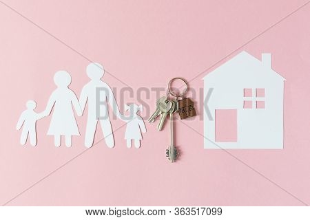 Composition With Paper Family Cutout And Paper House With Key And Keychain In A House Shape Top View