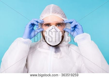 Doctor Or Lab Scientist Wearing Biohazard Protective Suit Puts On Safety Glasses, Close-up Of Face.