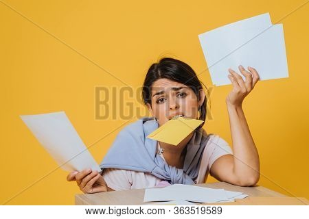 Young Girl Bewilderment Holding Several Envelopes And Sitting On A Yellow Background At The Table