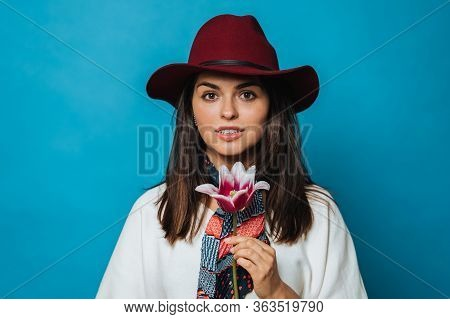Attractive Young Lady Holds Flower, Looking In Love, Dressed In White Sweater, Burgundy Hat With A B