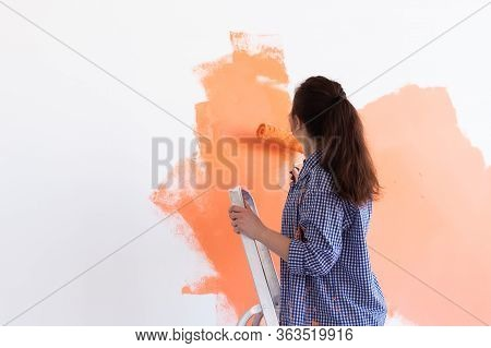 Renovation, Redecoration And Repair Concept - Cheerful Woman Painting Wall In New Home. Copy Space.