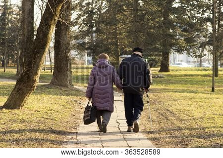 Old Elderly Couple Retired Spouses Walk In The Park Holding Hands