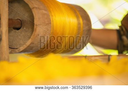 Wheel Spinning Yarn With Yellow Thread To Work For Weaving Machine And Thai Traditional Silk.