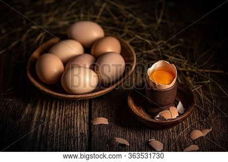 Whole And Broken Raw Brown Eggs On Wooden Table
