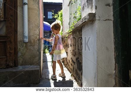 Sozopol, Bulgaria-september 18, 2019. A Little Girl And A Bright Sun In A Narrow Gap Between The Hou