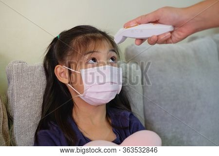 A Mother Periodically Monitoring Her Daughter's Temperature Using An Infrared Thermometer At Her For