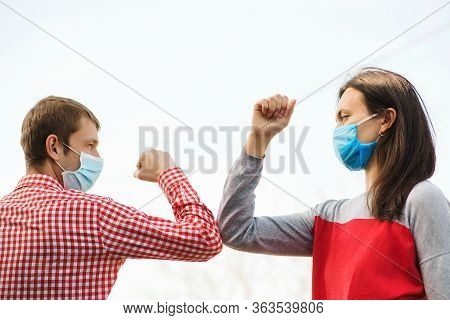 Young Couple Wear Face Masks Outdoors. Social Distancing. Friends Greeting With Elbows Outdoors. New