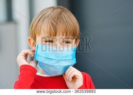 Little Boy Putting On Face Protective Mask Outdoors. Coronavirus Outbreak. Covid19. Coronavirus And