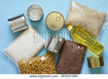 Food Delivery. Food Donation And Mask On A Blue Background: Oil, Buckwheat, Aris, Sugar, Canned Food