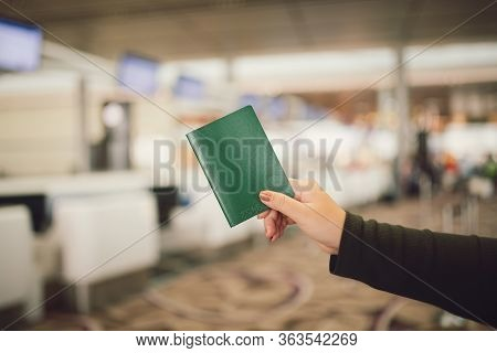 A Close Up Of A Woman With A Passport In The Airport Area Waiting To Check In