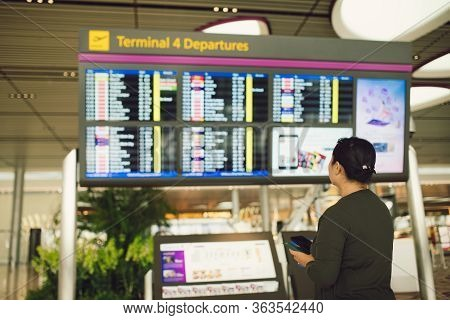 Passenger Traveling At The Flight Information Board In Airport Terminal Waiting Hall Area Checking T