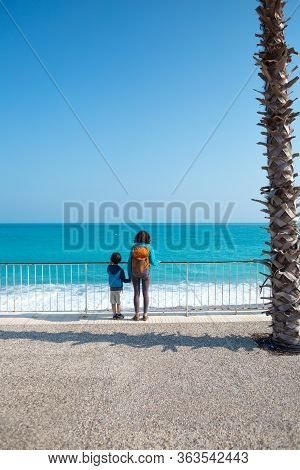 A Boy With His Mother Stand On The Promenade And Look At The Water.