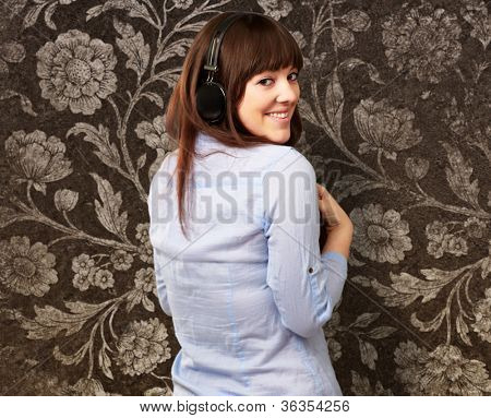 Happy Woman Wearing Headphone On Wallpaper