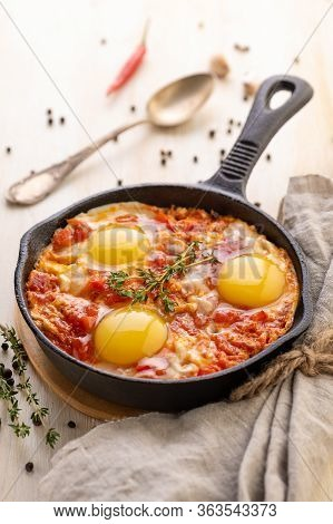 Shakshuka. Fried Eggs With Tomatoes And Sweet Pepper And Herbs In A Serving Cast-iron Frying Pan. Tr