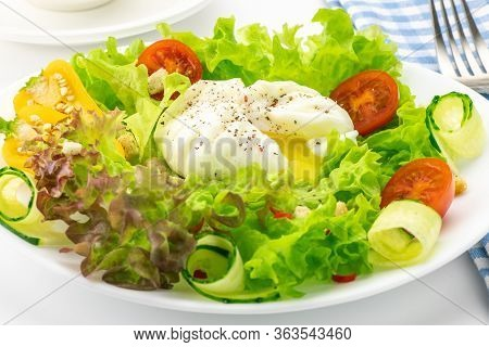 Vegetable Salad With Poached Egg. A Boiled Egg Is Laid Out On A Plate With Fresh Lettuce. Close-up.