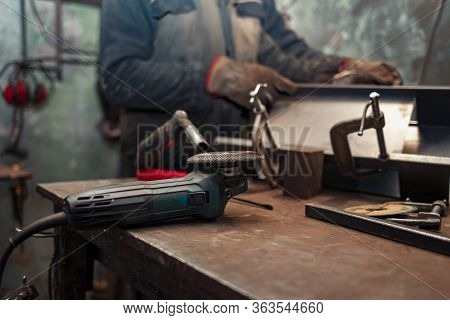 Man Clamps Iron Products Into C-clamps. Man Works With Clamps. Steel Workshop Concept