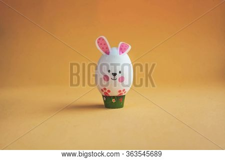 White Egg In The Form Of An Easter Bunny On A Brown Background