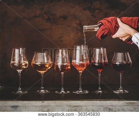 Rose Wine Glasses And Womans Hand Pouring Wine From Bottle