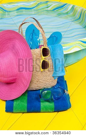 A straw beach bag full of accessories rests on a beach towel next to a children's plastic swimming pool. Good for summer vacation inferences.