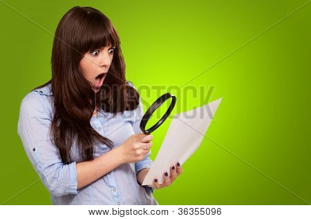 Portrait Of A Girl Holding A Magnifying Glass And Paper On Green Background poster