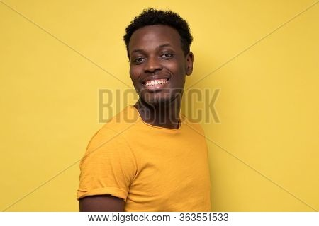 Young African Man Posing In Front Of Camera On Yellow Background.