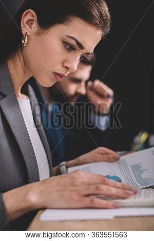 Selective Focus Of Data Analyst Working With Calculator And Charts On Paper Near Colleague On Black