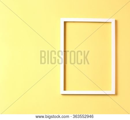 White Photo Frame On Pastel Yellow Color