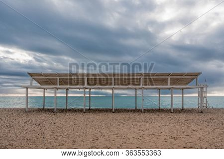 Wooden White Sunshades And Sand Beach With Azure Sea, Cloudy Sky Background The End Of The Beach Sea