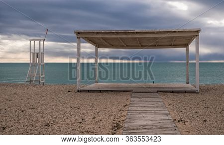 Wood Rescue Observation Post And Sunshades And Sand Beach With Azure Sea, Cloudy Sky Background. Emp