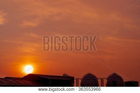 Industrial Gas Storage Tank. Lng Or Liquefied Natural Gas Storage Tank. Red And Orange Sunset Sky. S