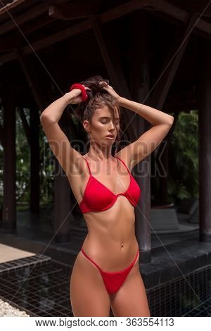 Beautiful Brunette Girl In Red Swimsuit Posing In Tropical Location With Green Trees. Young Sports M