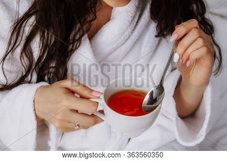 Photo Girl Stirs Tea With A Spoon. Mix Sugar In Tea. Female Hands Hold A Cup With Red Tea.