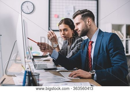 Side View Of Information Security Analyst Pointing At Computer Monitor To Colleague In Office